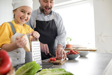 Smiling Girl Using Grater While Standing By Man In Kitchen At Home