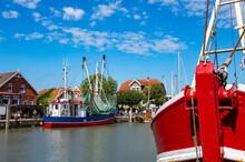 Germany, Lower Saxony, Neuharlingersiel, Fishing Boats Moored Along Town Harbor On Sunny Day