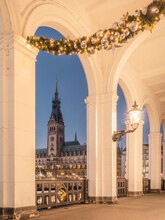 Germany, Hamburg, Alster Arcades With Christmas Decorations And View Of Town Hall At Dawn