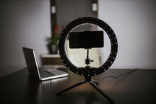 Smart Phone With LED Ring Light And Laptop On Table