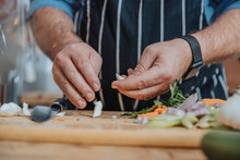Male Chef Wearing Apron Peeling Garlic While Doing Preparation Standing In Kitchen