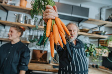 Chef Holding Organic Carrot While Standing With Colleague At Kitchen