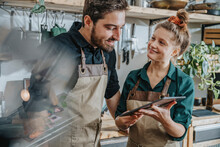 Smiling Chef Using Digital Tablet While Standing By Colleague In Kitchen
