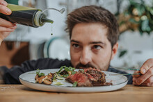 Expertise Adding Sauce Over Cooked Tomahawk Steak In Plate While Working In Kitchen