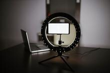 Illuminated Smart Phone On LED Ring Light Tripod At Table
