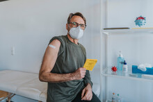 Male Patient Wearing Protective Face Mask With Bandage On Arm Holding Vaccination Certificate While Sitting At Examination Room