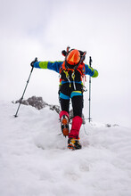 Trekker Climbing Snowcapped Mountain With Crampons And Hiking Poles