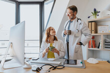 Doctors Smiling While Having Coffee At Office