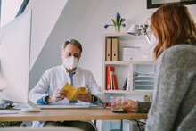 Doctor Wearing Protective Face Mask Checking Patient's Vaccination Certificate While Sitting At Office