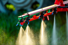 Close-up Of Tractor With Crop Sprayer Sprinkling Fertilizer In Farm