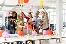 Female Business Professional Taking Selfie While Celebrating Birthday With Colleagues In Office