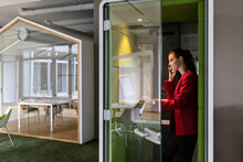 Smiling Female Entrepreneur Using Laptop While Talking On Mobile Phone In Soundproof Cabin At Office