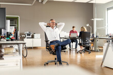 Smiling Male Business Professional With Hands Behind Head Looking Away While Sitting On Chair In Office