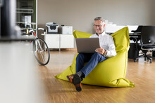 Smiling Businessman Using Laptop While Sitting On Beanbag In Office