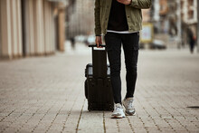 Man With Suitcase Walking On Footpath