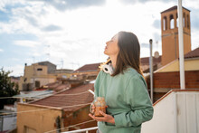 Woman With Eyes Closed Holding Fruit Smoothie While Standing At Balcony