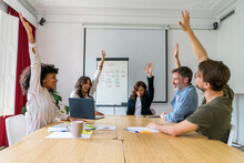 Cheerful Male And Female Entrepreneurs With Arms Raised In Board Room At Office