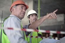 Two Male Construction Workers Talking At Construction Site