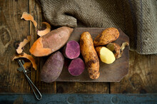 Different Types Of Potatoes: Sweet Potato, Annabelle, Purple Sweet Potato Against Rustic Background