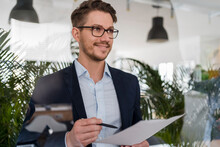Smiling Male Entrepreneur With Document Seen Through Glass At Office