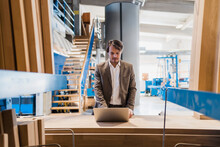 Young Businessman Working On Laptop While Standing At Industry