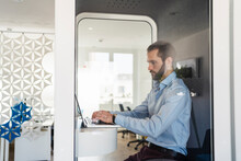 Male Professional Working On Laptop While Sitting In Telephone Booth At Office