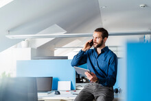 Professional With Digital Tablet Talking On Mobile Phone While Sitting At Office