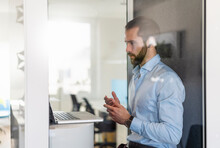 Male Professional Having Discussion On Video Call Over Laptop In Telephone Booth At Office