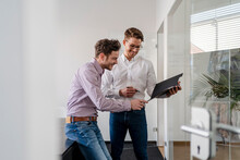 Smiling Male Colleagues Discussing Over Clipboard At Office