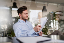 Businessman Analyzing Document While Working At Office