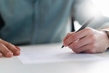 Businessman With Pen Filling Document At Office