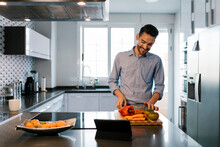 Smiling Man With Vegetables Standing At Kitchen Counter