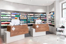 Checkout Counters Against Shelves With Medicines At Pharmacy