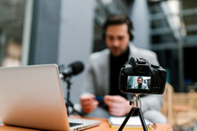 Businessman Filming Vlog Through Camera While Sitting At Cafe