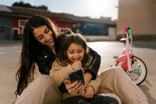 Smiling Mother Using Mobile Phone While Sitting On Road
