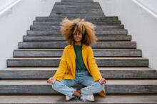 Afro Woman In Lotus Position Sitting On Staircase