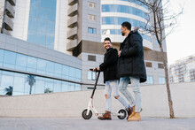Mid Adult Man With Electric Scooter Smiling At Male Friend While Walking Through City