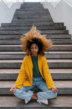 Afro Woman With Tousled Hair Meditating While Sitting On Staircase