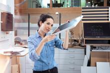 Female Entrepreneur Analyzing Solar Panel Model In Factory