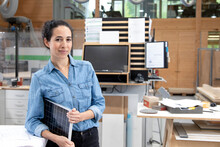 Businesswoman With Solar Panel Model In Factory