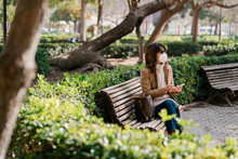 Mature Woman With Protective Face Mask Holding Mobile Phone While Sitting At Park