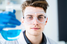 Young Scientist Wearing Protective Eyewear While Holding Flask With Chemical In Laboratory