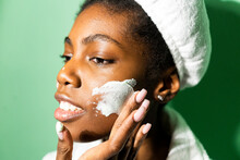 Close-up Of Woman Applying Cream On Face While Standing Against Green Background