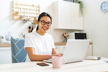 Smiling Woman Sitting By Table With Laptop At Home