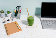 Laptop, Healthy Green Juice, Book And Succulent Plant Over Desk
