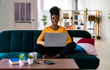 Young Afro Woman Using Laptop While Sitting Cross-legged On Sofa In Living Room At Home