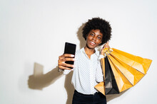 Young Smiling Woman With Shopping Bags Taking Selfie Through Smart Phone While Standing Against White Background