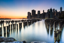 Twilight Over The East River And Lower Manhattan And The Pilings By Brooklyn Bridge Park, New York City