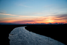 Water Flows Through The Prairie At Sunset On The Blackfeet Indian Reservation, MT.
