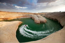A Woman Rides A Jet Ski Through A Winding Red Rock Canyon In Lake Powell, UT